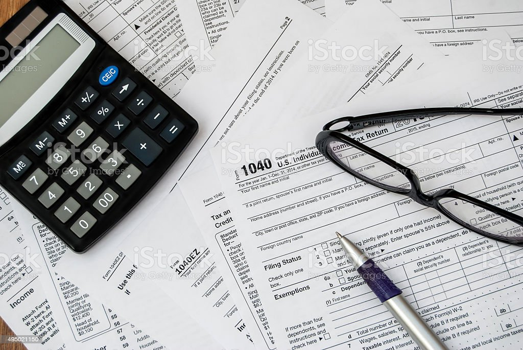 pen, glasses and calculator on the tax form stock photo