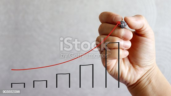 istock A pen hand drawing a red arrow and black bar graph. 903552098