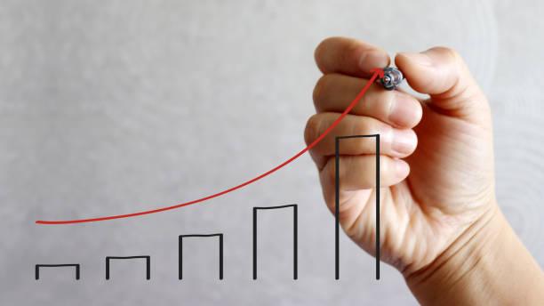 a pen hand drawing a red arrow and black bar graph. - diagramma a colonne foto e immagini stock
