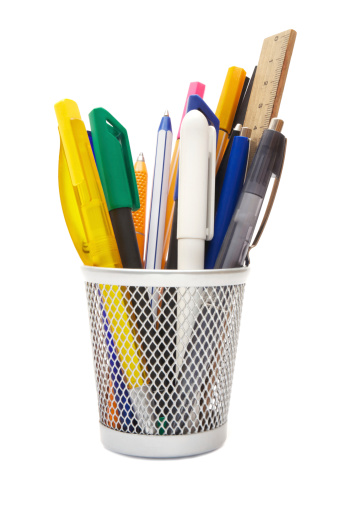 Various writing instruments in a wire mug. Isolated on a white background.