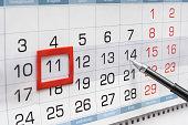 Pen indicates future friday on wall calendar