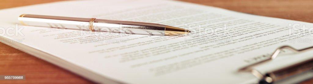 Stylo allongé sur une forme de contrat ou de la demande, vue grand angle. photo libre de droits