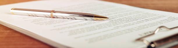 ручка, лежащая на договоре или форме заявки, широкоугольный вид. - письмо документ стоковые фото и изображения