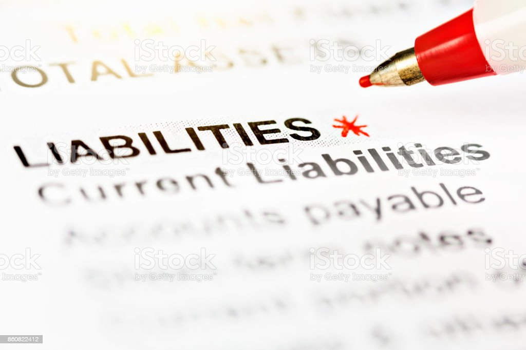 Pen marks 'Liabilities' in financial document with asterisk stock photo