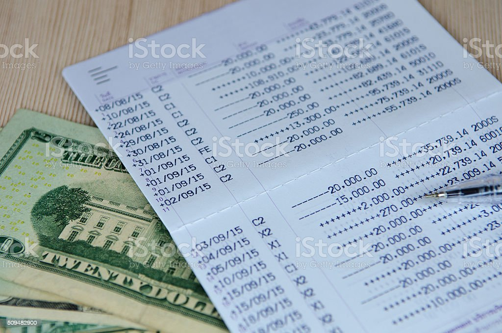 Pen on bank account passbook with dollar banknote, selective foc stock photo