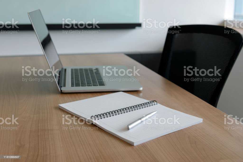 Pen on notepad and laptop and for agenda kept on table in empty...