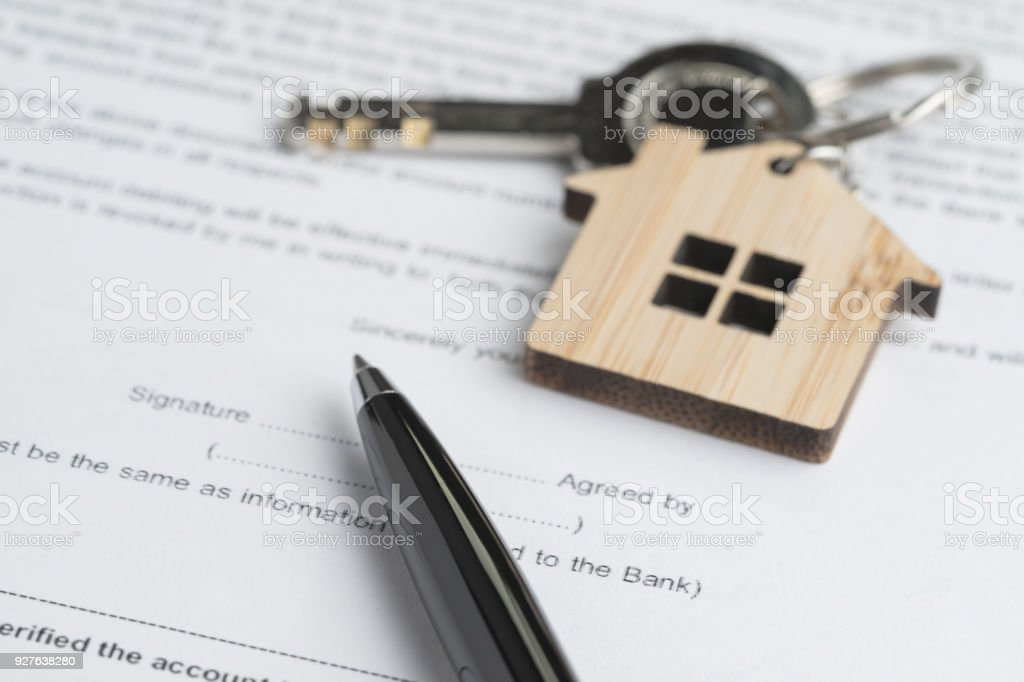 pen on sign agreement contract paper document with key