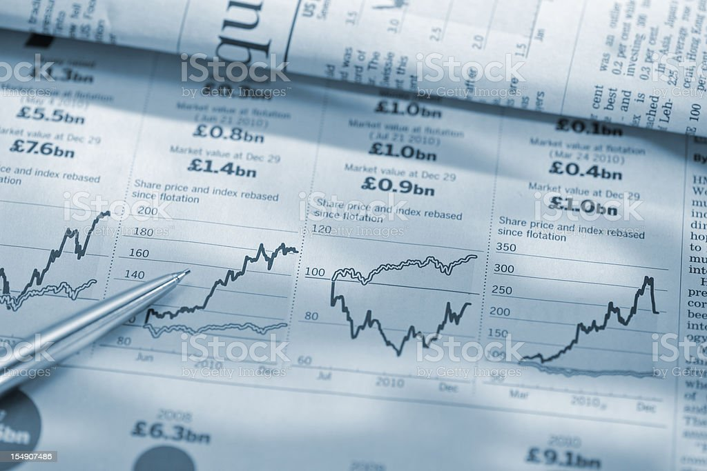 pen on stock price graphs in financial newspaper royalty-free stock photo
