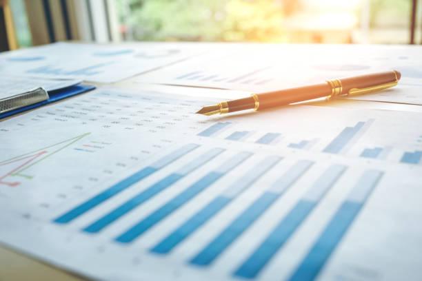 Caneta sobre o papel do negócio. Gráfico do relatório - foto de acervo