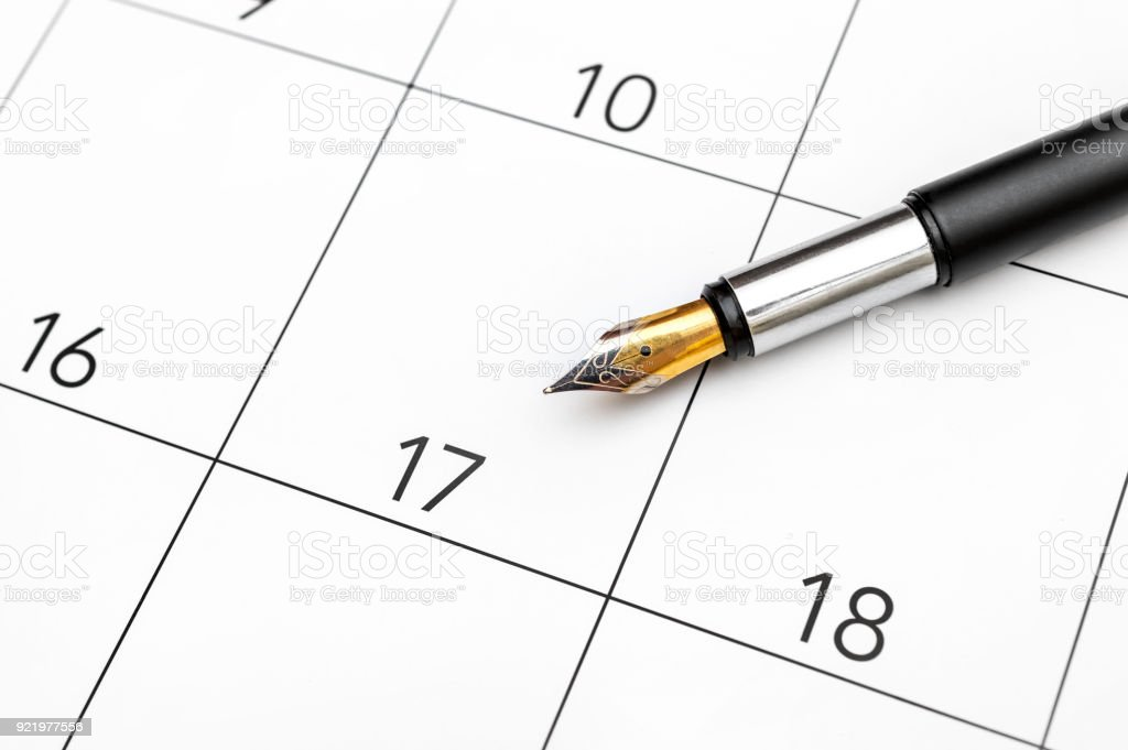 Pen on the calendar. Close up. Pen pointing on day 17 of the month at...