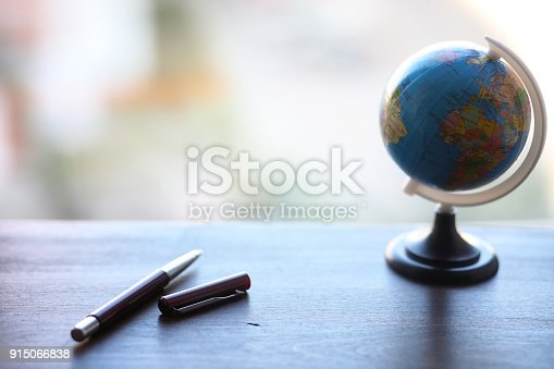 istock A pen on the desk and a small globe 915066838