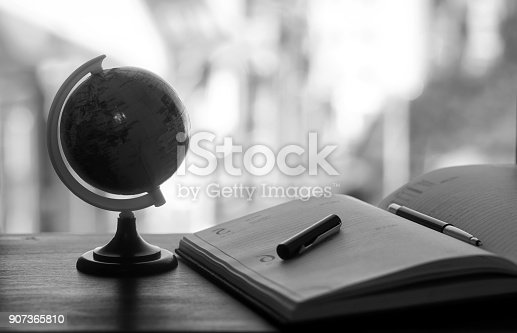 istock A pen on the desk with small globe 907365810