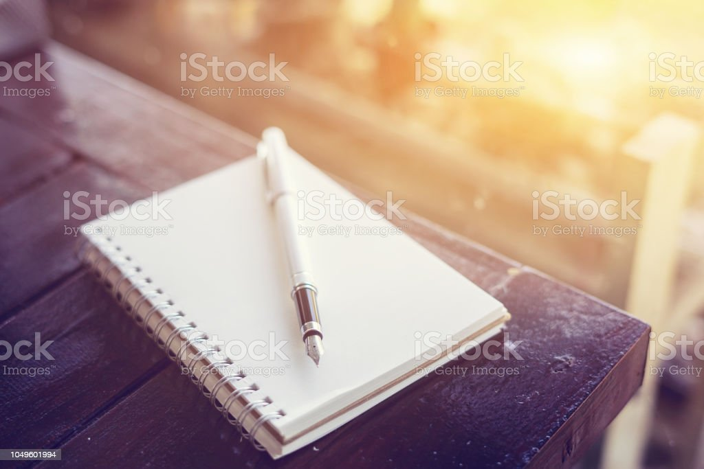 pen on the desk,Open a blank white notebook on wooden table and green bokeh background ,vintage color,selective focus - Стоковые фото Архивная папка роялти-фри