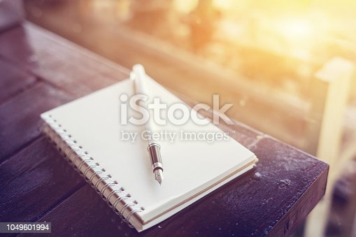 pen on the desk,Open a blank white notebook on wooden table and green bokeh background ,vintage color,selective focus