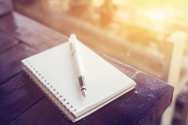 długopis na biurku, otwórz pusty biały notatnik na drewnianym stole i zielonym tle bokeh, kolor vintage, selektywne ustawianie ostrości - notes zdjęcia i obrazy z banku zdjęć