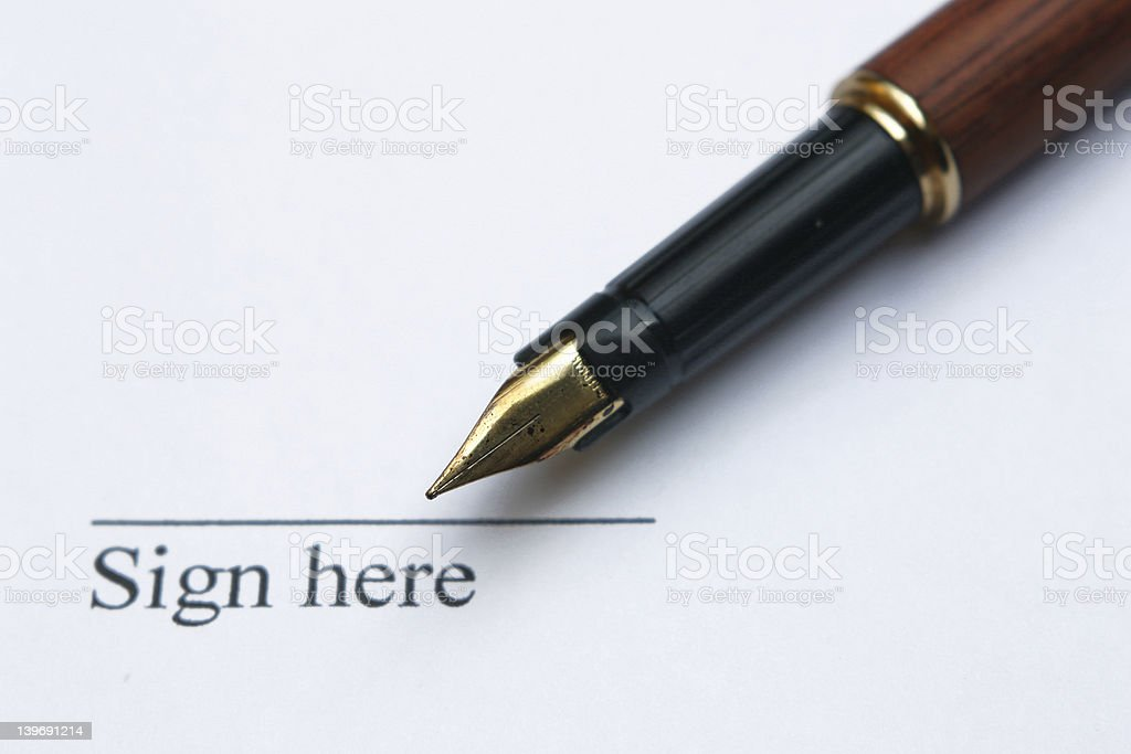 A pen pointing to a space for someone to sign stock photo