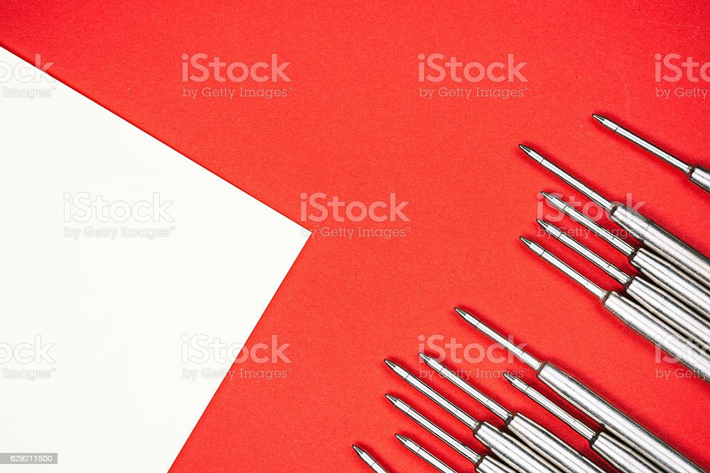 Pen refills over red and white stock photo
