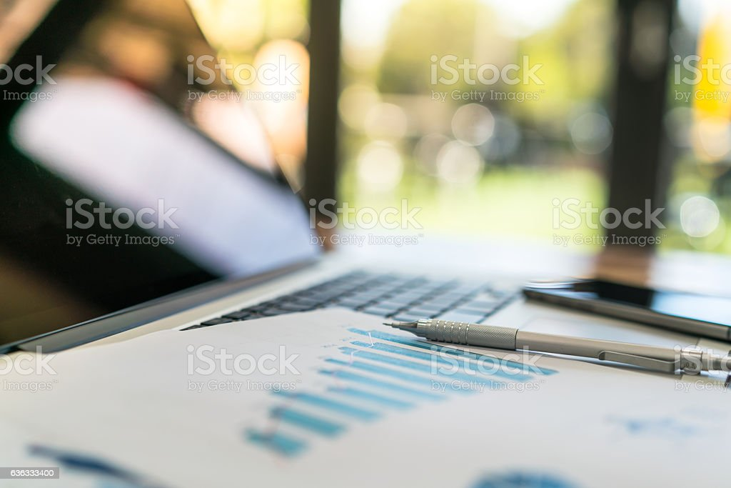 Pen with a financial report on Laptop stock photo