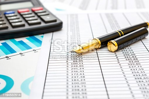 531581605 istock photo Pen with calculator on financial graph and documents. 1194532514