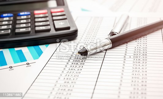 istock Pen with calculator on financial graph and documents. Toned image. 1128971882
