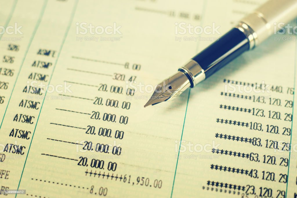 Pen with Finances statement ,hand pointing business charts,coins on paper work in the office,discussing stock marketing document,book bank stock photo