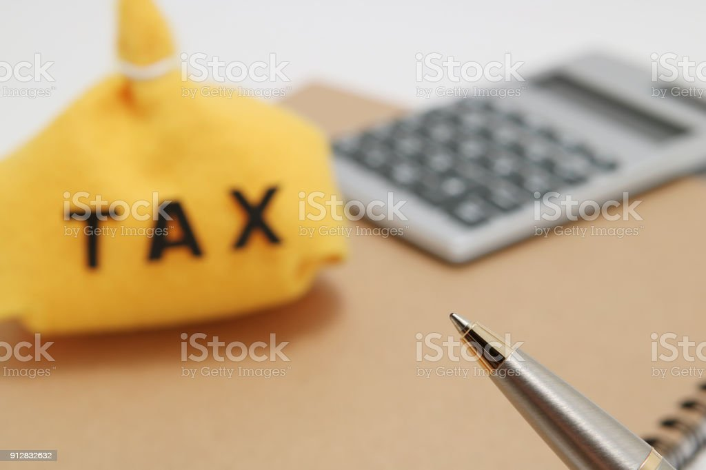 Pen with money bag and caluculator in the background. stock photo