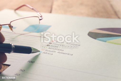 istock pen with summary report and eyeglasses on table office. 647506938