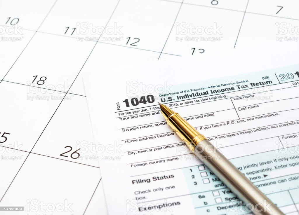 Pen with tax forms on the calendar.
