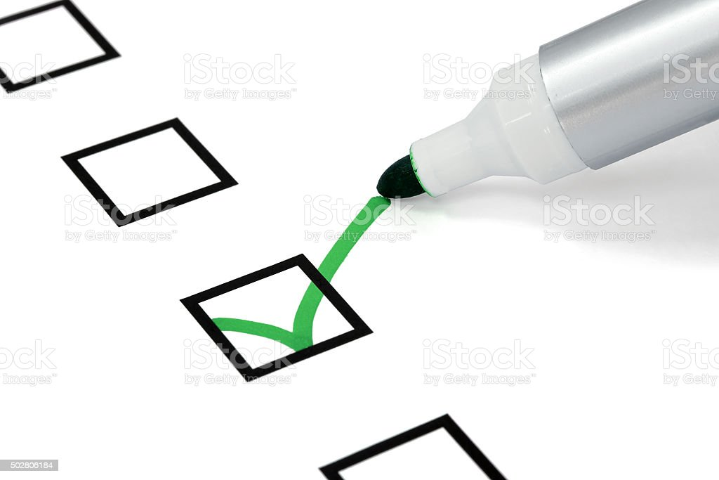 Pen writing a green check mark stock photo
