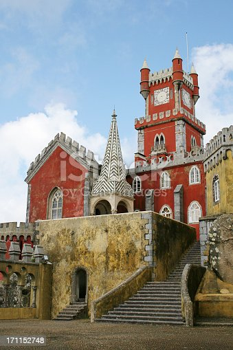 Detail of the Palacio da Pena at Sintra in Portugal. The buildings are painted red and ochre.  A stone staircase leads from lower centre of the frame up to the palace.Another image of this palace: