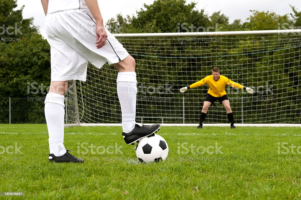 Soccer player gets ready for penalty shoot out. Goalkeeper is ready...