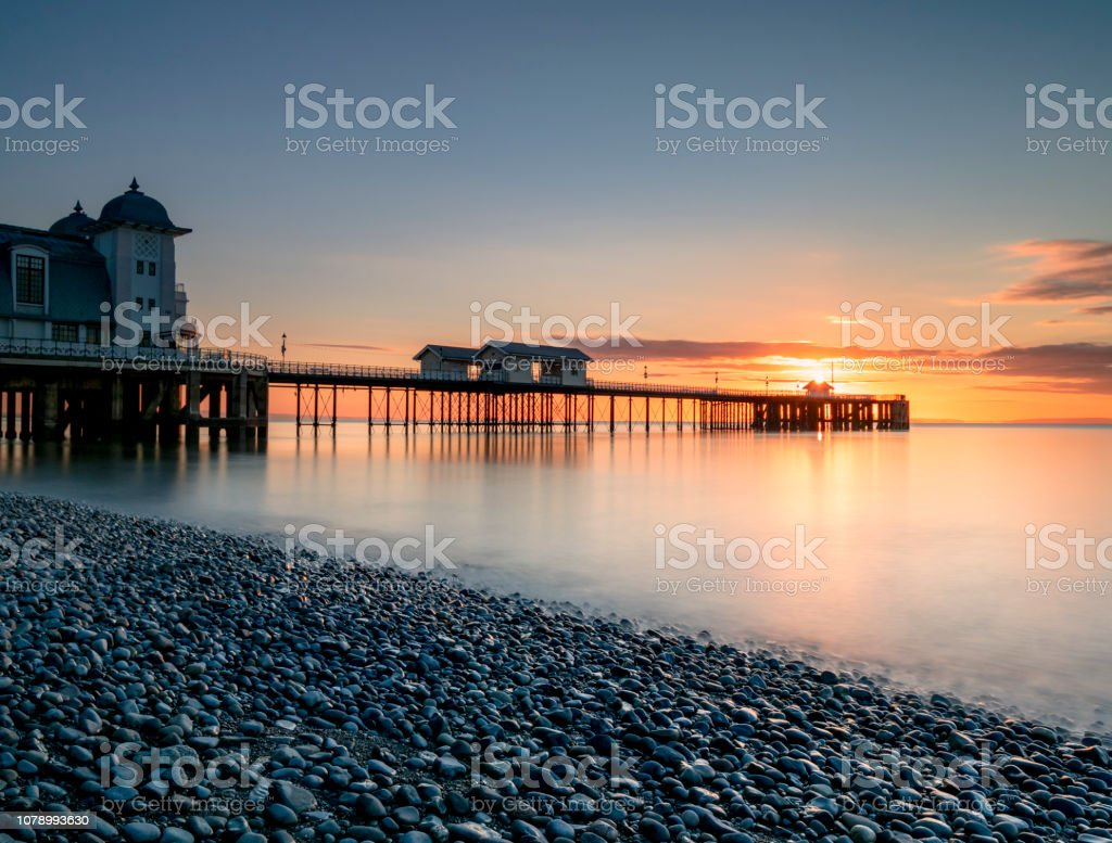 Penarth pier from the pebble shoreline at sunrise. stock photo