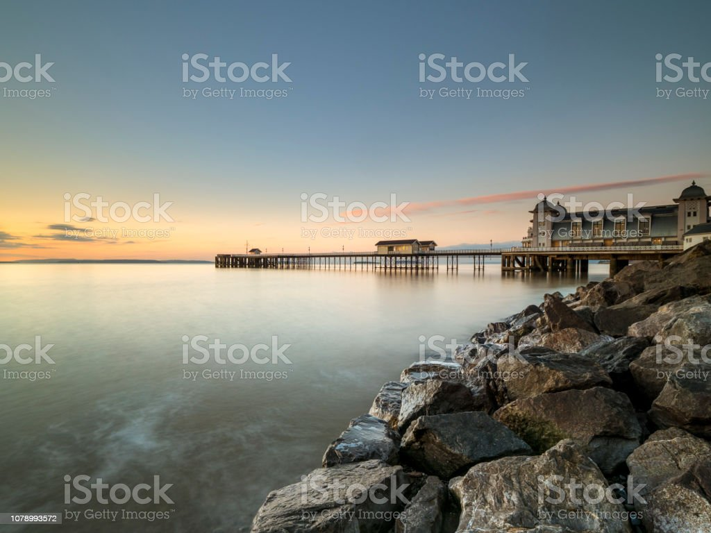 Penarth Pier from the shoreline rocks at high tide. stock photo