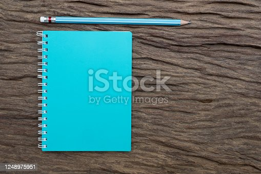 Pencil and book mockup on the old wood desk at the background, Flat lay photo, top view