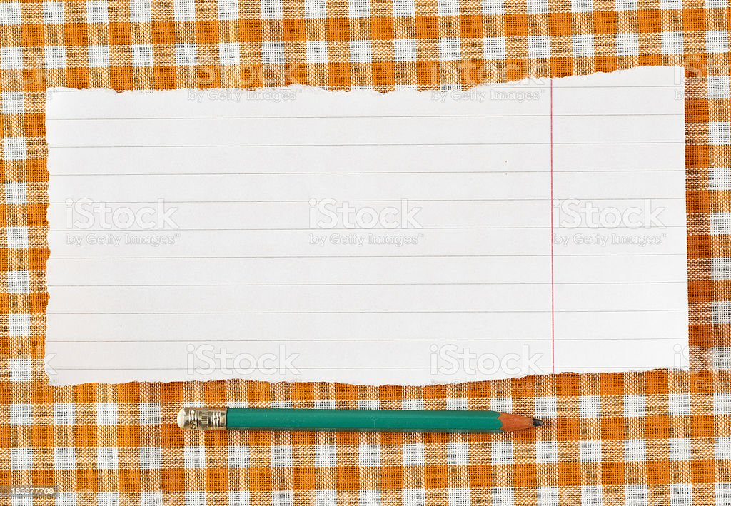 Pencil and paper on orange tableclot royalty-free stock photo