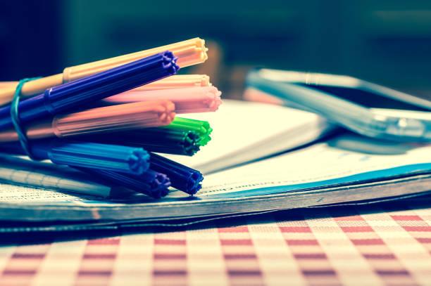 Pencil case, felt tip colouring pens, homework books and smart phone stock photo