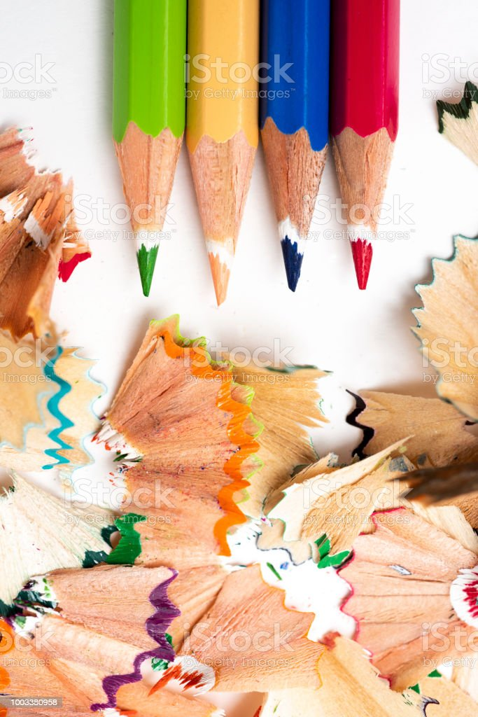 high angle view of some pencil crayons of different colors and a pile...
