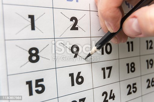 Pencil crosses out dates on the wall calendar