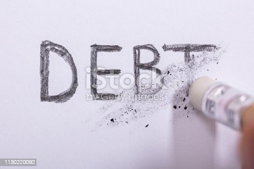 Close-up Of Pencil Eraser Erasing Debt Word On White Paper