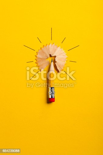 Photography of a pencil on yellow paper arranged to a light bulb.