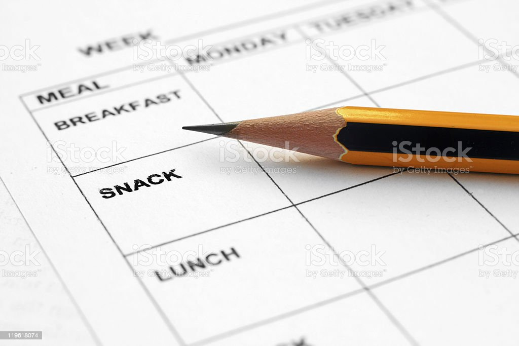A pencil lying on a blank weekly meal planner stock photo