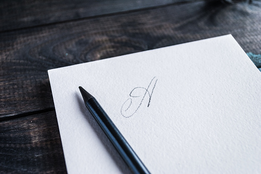 Pencil lying on open notepad with letter on first page