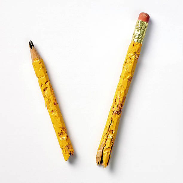 Pencil nibbled and broken in two on white background stock photo