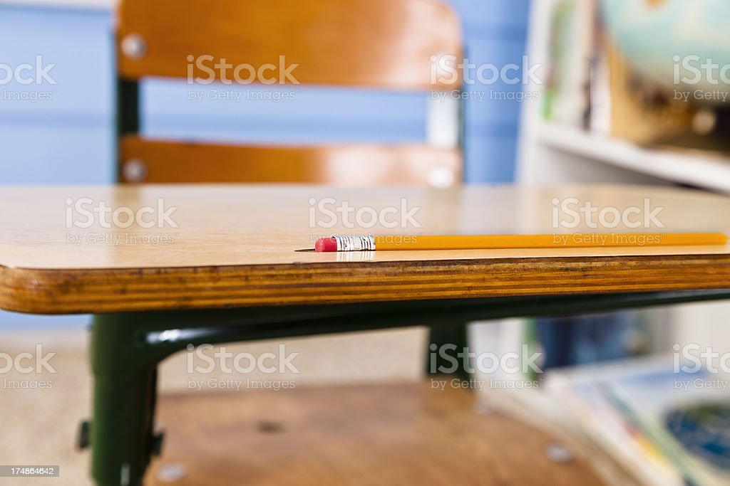 Pencil on student desk in a classroom with brick background royalty-free stock photo