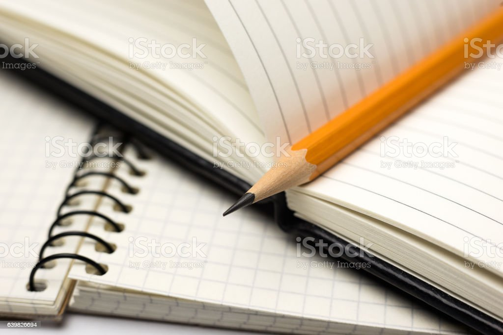 Pencil on the pages of an open notebook for records stock photo