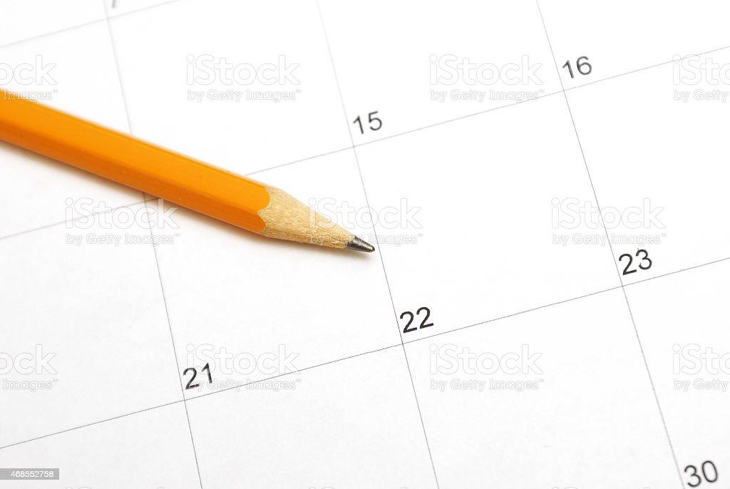 Pencil on top of blank calendar stock photo
