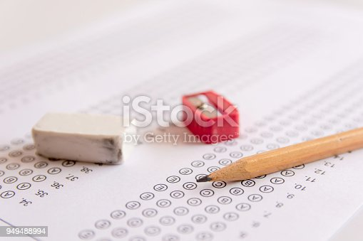istock Pencil, Sharpener and eraser on answer sheets or Standardized test form with answers bubbled. multiple choice answer sheet 949488994