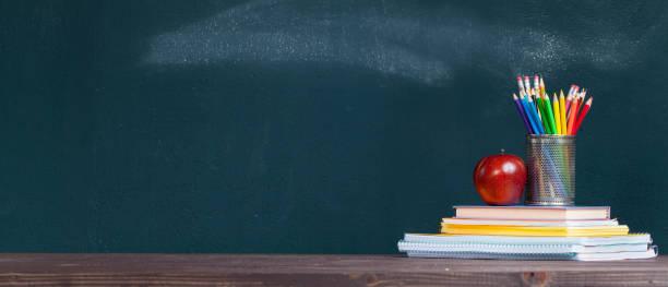 bandeja do lápis e uma maçã em cadernos na mesa do professor da escola - professor - fotografias e filmes do acervo