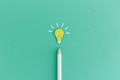 Creative composition of pencil with small paper light bulb glowing above on green background