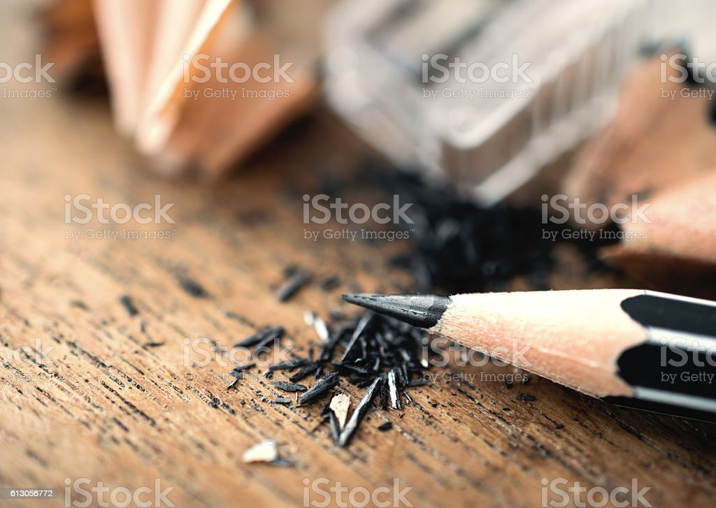 pencil with sharpening shavings, on wooden table.. stock photo